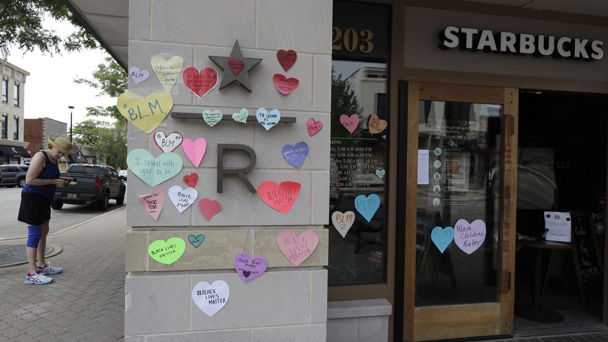 """In this Thursday, June 4, 2020 file photo, a woman looks at the plywood covering the windows of a Starbucks store in downtown Naperville, Ill., as Naperville residents used hearts to post messages in support of the Black Lives Matter movement. Starbucks is the latest company to say it will pause social-media ads after a campaign led by civil-rights organizations called for an ad boycott of Facebook, saying it doesn't do enough to stop racist and violent content.  Starbucks said Sunday, June 28 that its actions were not part of the """"#StopHateforProfit"""" campaign, but that it is pausing its social ads while talking with civil rights organizations and its media partners about how to stop hate speech online."""