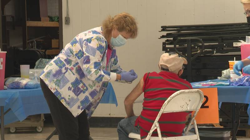 A healthcare worker puts a bandaid on a man's arm after administering the shot.