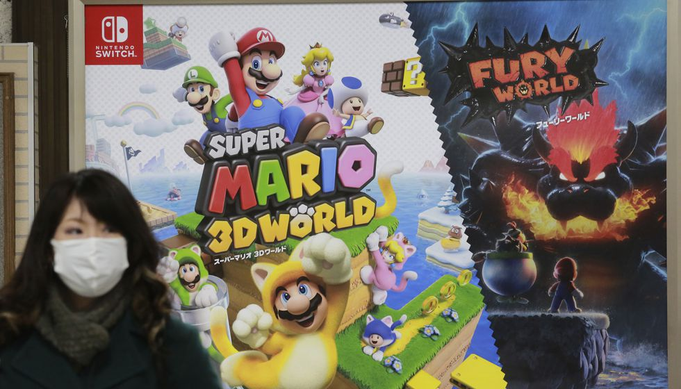 A woman walks by posters of Nintendo in Tokyo, Monday, Feb. 1, 2021.