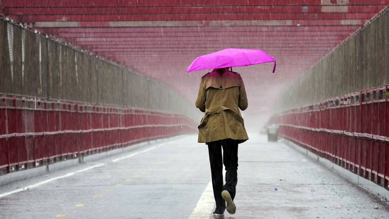 A pedestrian walks during a heavy downpour of rain over the Williamsburg bridge, Tuesday, Oct....