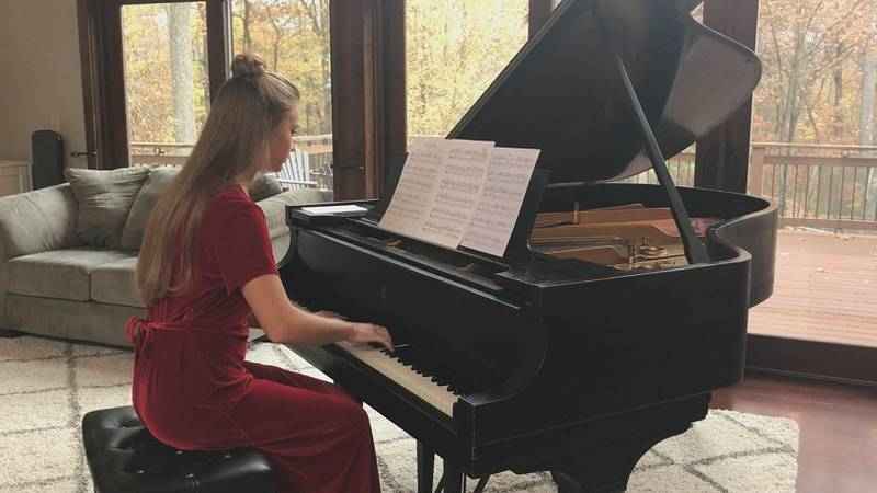 Grace performs piano in front of an audience