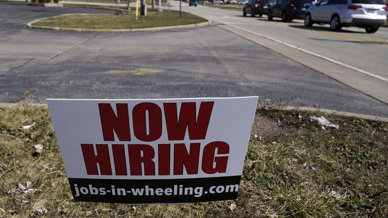 A hiring sign shows in Wheeling, Ill., Sunday, March 21, 2021.  With viral cases declining,...