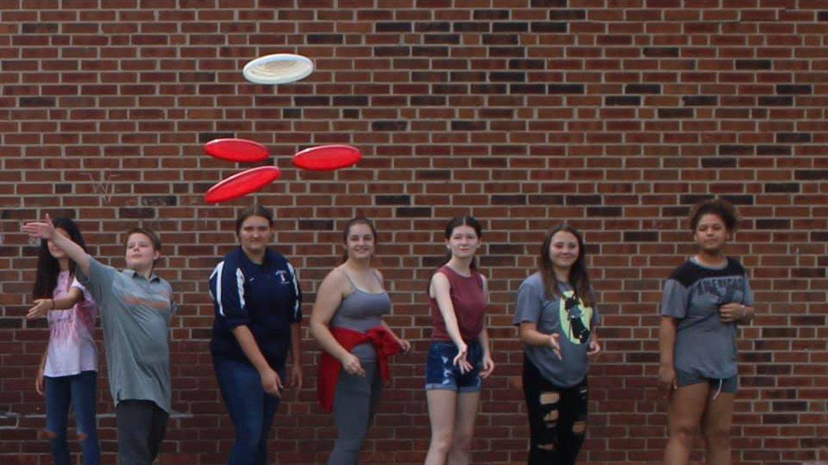 """Van Devender Middle School students """"launching"""" frisbee UFOs."""