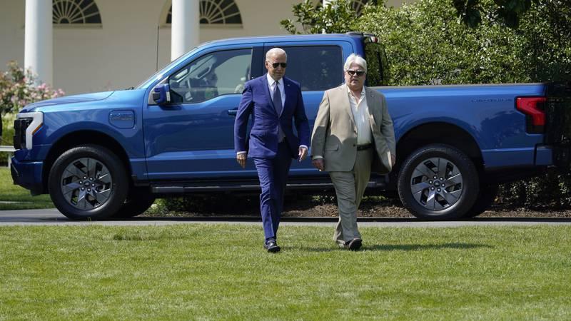 President Joe Biden walks with United Auto Works Local 600 president Bernie Ricky before he...