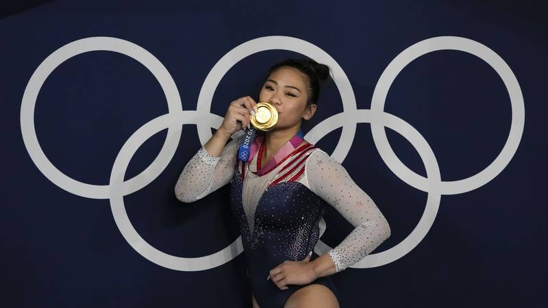 Sunisa Lee, of United States, reacts as she poses for a picture after winning the gold medal in...