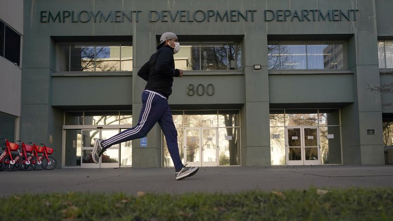 In his Dec. 18, 2020 file photo a runner passes the office of the California Employment...