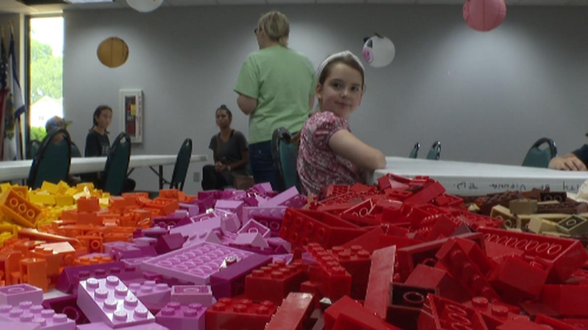 Lilyanna Chamberlin gazes at a pile of legos