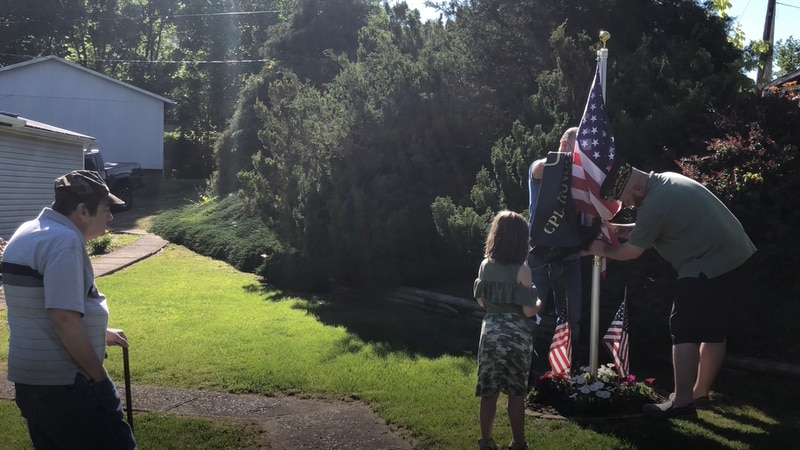 Gary Thomas watches as a flag is hoisted in honor of his father and grandfather