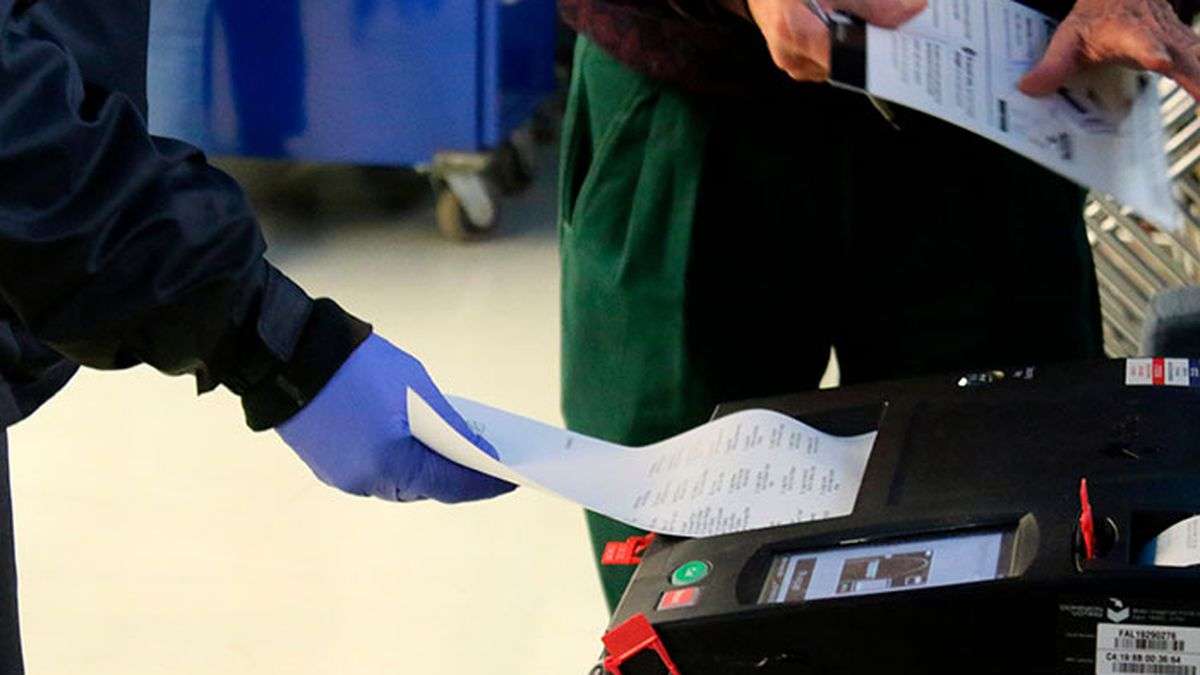 In this Saturday, March 14, 2020 photo, voters cast their ballots during early voting in Chicago while wearing protective gloves. Residents and poll workers took extra precautions amid concerns over the coronavirus. The Illinois state primary elections are scheduled for Tuesday, March 17. (Source: AP Photo/Noreen Nasir/AP)