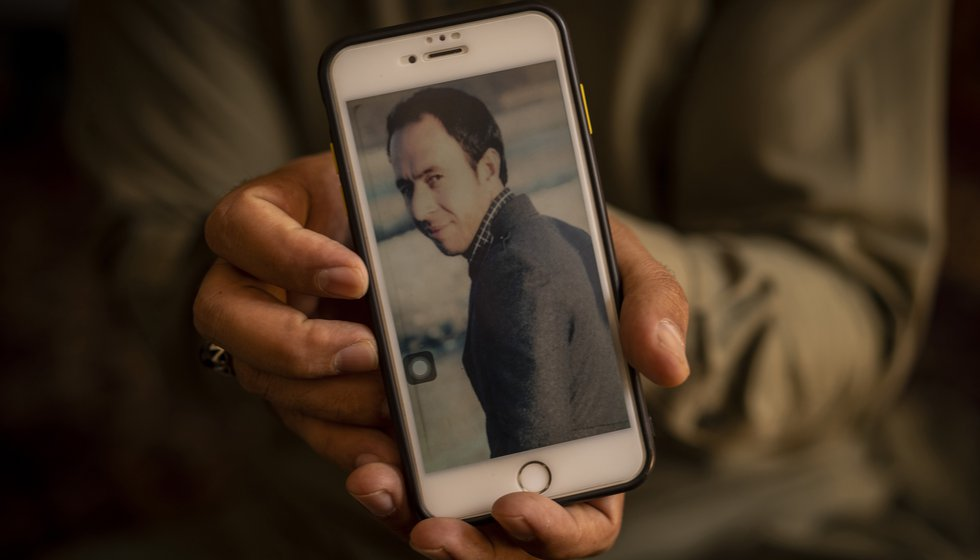 Emal Ahmadi, 32, holds a picture of his slain brother Zemerai Ahmadi at the family house in...