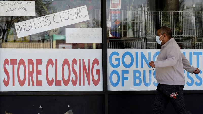 FILE - In this May 21, 2020 file photo, a man walks past signs displayed at a store closing due...