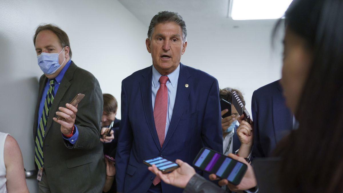 FILE - Sen. Joe Manchin, D-W.Va., is surrounded by reporters as senators rush to the chamber...