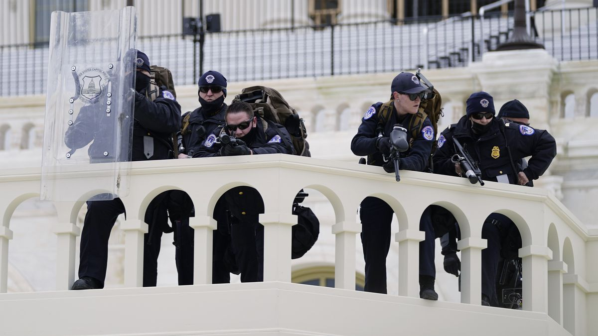 In this Jan. 6, 2021, file photo, police keep a watch on demonstrators who tried to break...