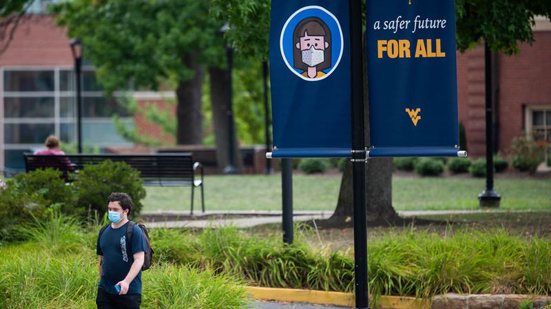 Student wearing a mask walks by a safety message on West Virginia University's Morgantown Campus.