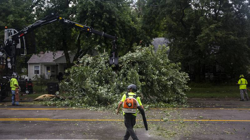 Des Moines city crews remove a tree fallen on Hickman Road, on Monday, Aug. 10, 2020, in Des...